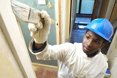 A young man wearing overalls and a hard hat painting a door frame