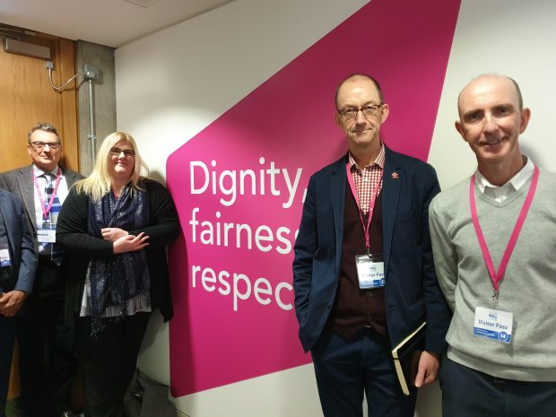 Social Security Advisory Committee members Bruce Calderwood, Victoria Todd, Phil Jones and Jim McCormick standing by a sign which says dignity, fairness and respect. Photograph taken at Social Security Scotland in Dundee.
