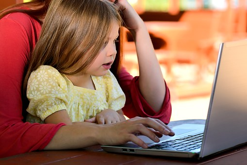 Image of adult working on laptop with child on lap